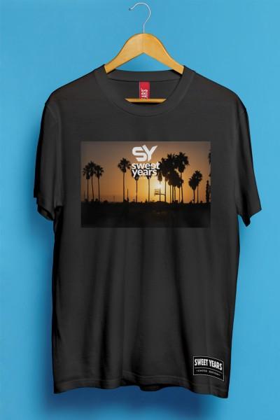 T-shirt Sweet Years da uomo in cotone con grande stampa multicolor di un tramonto con palme sullo sfondo.